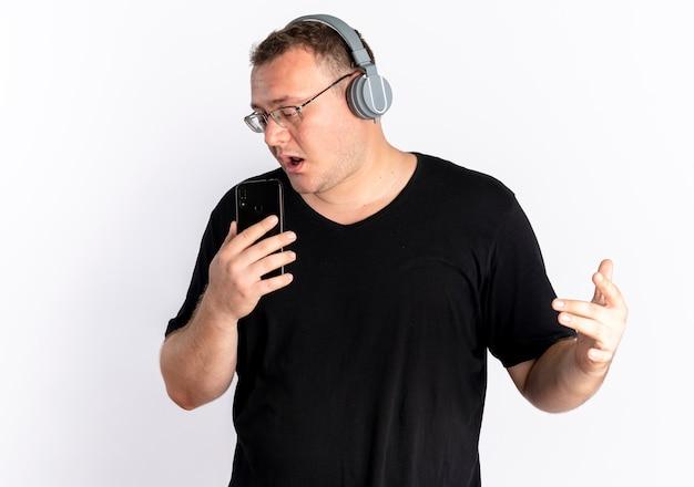 Nadwaga mężczyzna w okularach na sobie czarną koszulkę ze słuchawkami, używając swojego smartfona jako mikrofon śpiewający stojąc na białej ścianie
