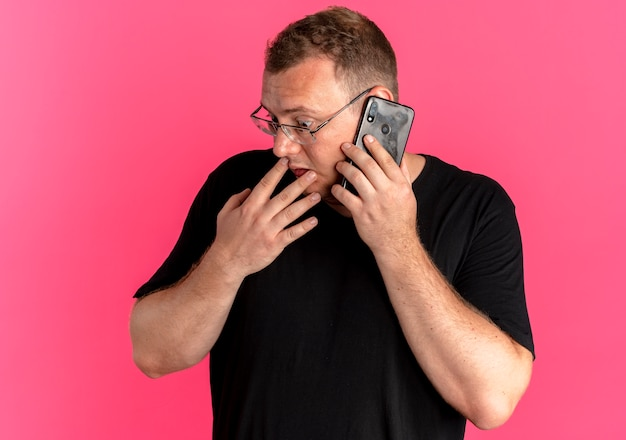 Nadwaga mężczyzna w okularach na sobie czarny t-shirt patrząc na bok zdezorientowany podczas rozmowy przez telefon komórkowy na różowo