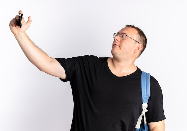 Nadwaga mężczyzna w okularach na sobie czarny t-shirt przy selfie przy użyciu swojego smartfona stojącego na białej ścianie