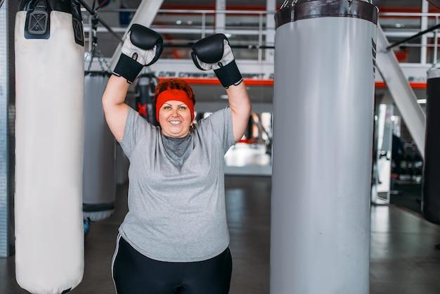 Nadwaga spocona kobieta w rękawicach bokserskich przeciwko worek treningowy w siłowni.