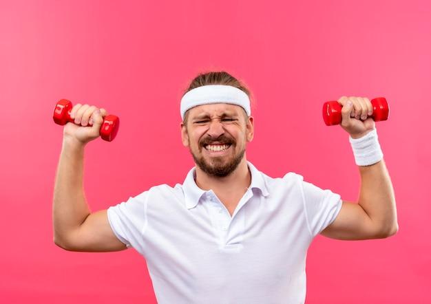 Nadwyrężony młody przystojny sportowy mężczyzna nosi opaskę i opaski na rękę podnosząc hantle na białym tle na różowej przestrzeni