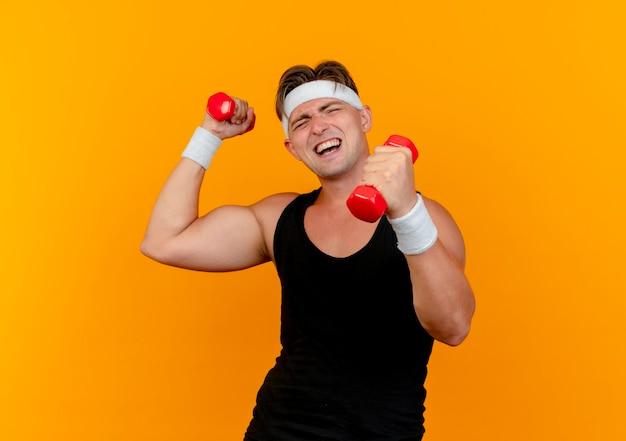 Nadwyrężony młody przystojny sportowy mężczyzna ubrany w opaskę i opaski na rękę podnosząc trzymając hantle na białym tle na pomarańczowej ścianie