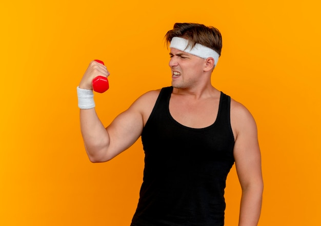 Nadwyrężony młody przystojny sportowy mężczyzna ubrany w opaskę i opaski na rękę, trzymając i patrząc na hantle na białym tle na pomarańczowej ścianie
