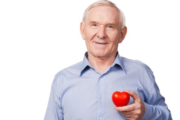 Nadzieja z wielkim sercem. uśmiechnięty starszy mężczyzna w koszuli trzymający podpórkę serca, stojąc na białym tle