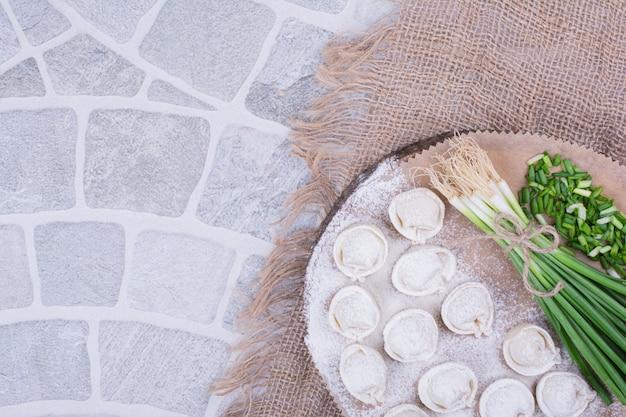 Nadzienia chinkali w mące podawane z pęczkiem zielonej cebuli.
