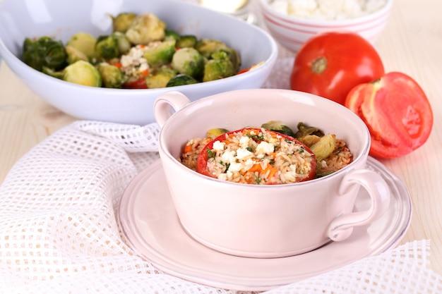Nadziewane pomidory na patelni i miskę na drewnianym stole z bliska