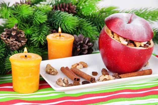 Nadziewane świąteczne jabłko z orzechami i rodzynkami na stole z bliska