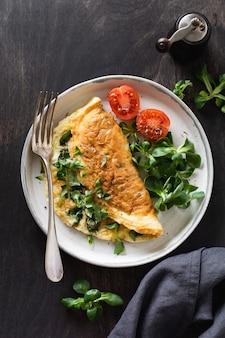 Nadziewany omlet z pomidorami, czerwoną papryką, twarogiem i roszponką lub roszponką na ciemnym drewnie z miejscem na kopię. zdrowa żywność dietetyczna na śniadanie. widok z góry, płaski układ.