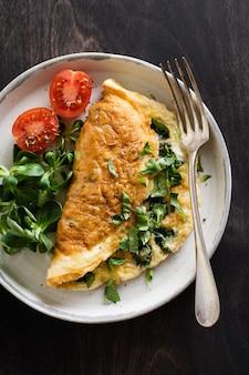 Nadziewany omlet z pomidorami, czerwoną papryką, twarogiem i roszponką lub roszponką na ciemnym drewnie z miejscem na kopię. zdrowa żywność dietetyczna na śniadanie.