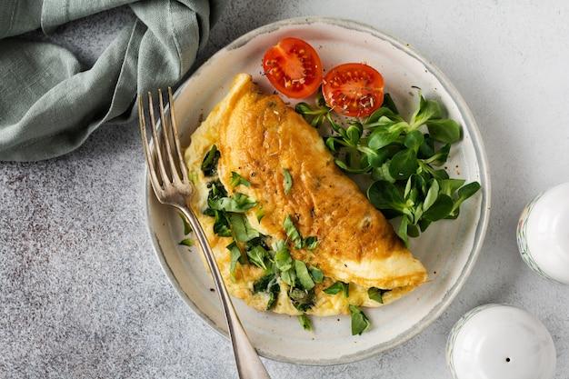 Nadziewany omlet z pomidorami, czerwoną papryką, twarożkiem i roszponką lub roszponką na jasnym betonie z miejscem na kopię. zdrowa żywność dietetyczna na śniadanie. widok z góry, płaski układ.
