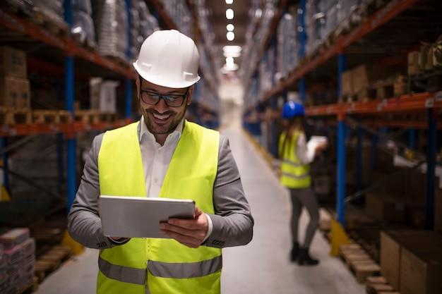 Nadzorca magazynu czytający raport na tablecie o udanej dostawie i dystrybucji w centrum logistycznym magazynu