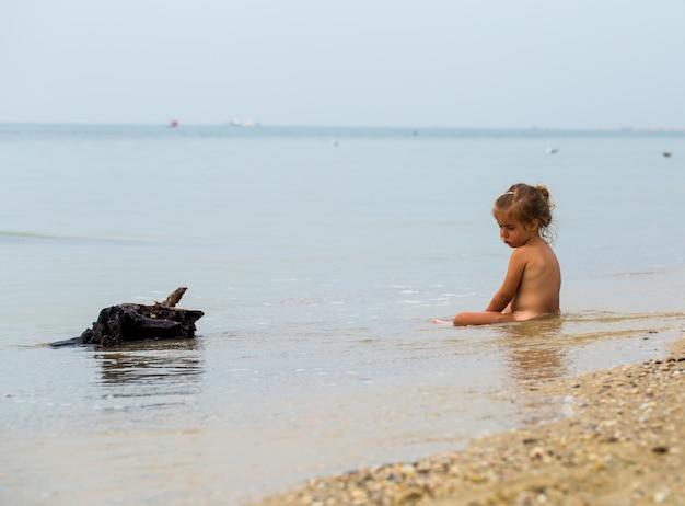 Naga dziewczynka bawi się w morzu, piękna plaża