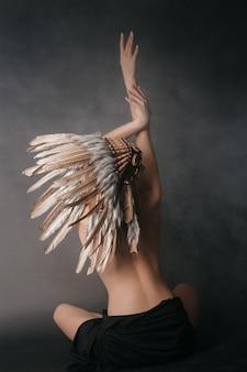 Naga idealna kobieta w stroju indian amerykańskich w dymie na szarej ścianie. kapelusz wykonany z piór. tajemniczy mistyczny sposób, seksowne ciało, piękne plecy