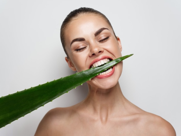 Naga kobieta gryząca liść aloesu na jasnym tle witaminy rośliny kosmetyki