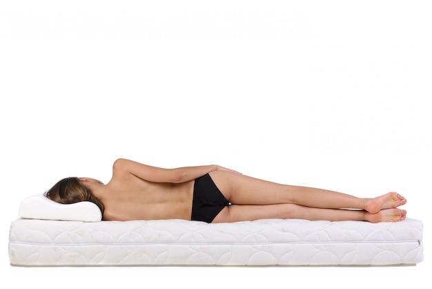 Naga kobieta leży na materacu.