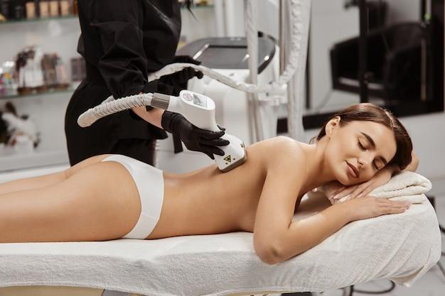 Naga kobieta w spa o masażu z profesjonalnym masażerem