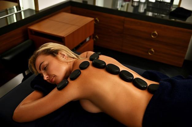 Naga kobieta z gorącymi kamieniami lawowymi wzdłuż kręgosłupa leżąca na stole do masażu podczas relaksu podczas ajurwedyjskiego zabiegu na ciało gorącymi kamieniami