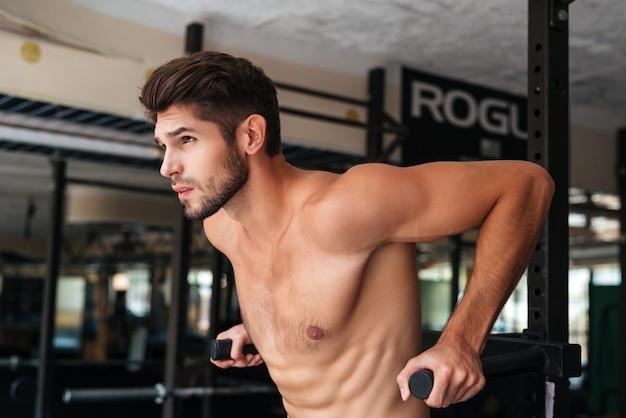 Naga modelka robi ćwiczenia na siłowni. odwracając wzrok