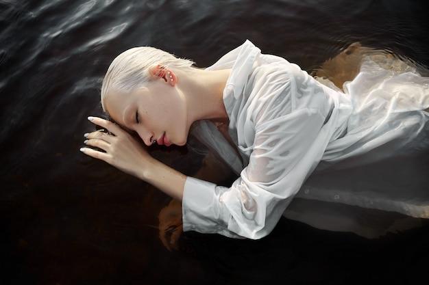 Naga naga seksowna kobieta w wodzie o zachodzie słońca. piękna blondynka z krótkimi mokrymi włosami i dużym biustem, portret artystyczny w morzu