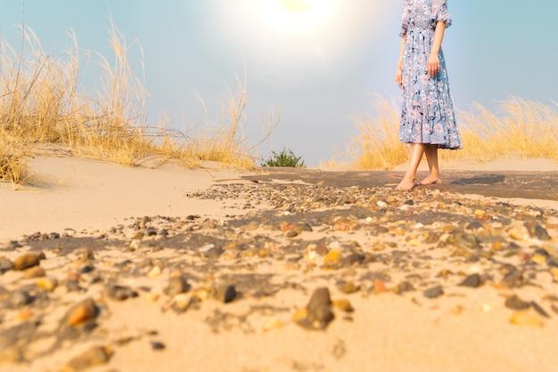 Naga stopa nieszczęśliwa kobieta chodzi na rockowej piasek drodze samotnie