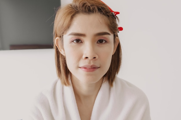 Naga twarz azjatyckiej modelki przygotowuje się do nałożenia makijażu od artysty