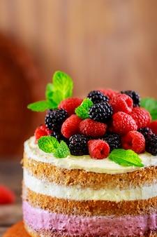 Nagi biszkopt z kremem waniliowym i świeżymi jagodami na białym stole.
