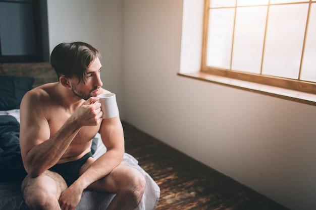Nagi brodaty przystojny mężczyzna o ciemnych włosach, trzymający filiżankę gorącej herbaty lub kawy w swojej sypialni. jest poranek.