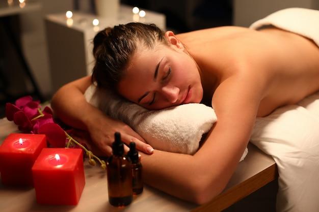 Nagi dziewczyna leżącego ręcznik przygotowuje się do masażu