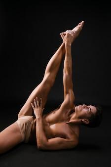 Nagi mężczyzna leży i dotyka przedłużonej nogi