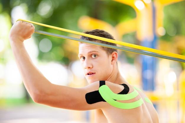 Nagi muskularny mężczyzna trenuje z zespołem oporu fitness w parku i boisku sportowym na tle