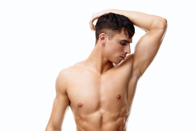 Nagi sportowiec z napompowanymi mięśniami fitness i rękami w pobliżu przyciętej twarzy
