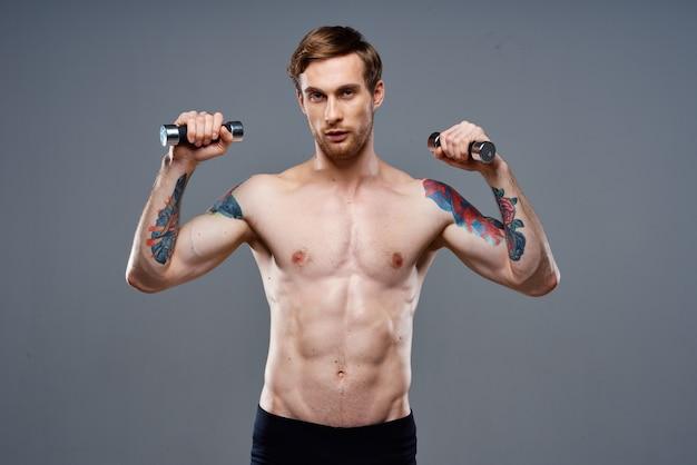 Nagi sportowiec z tatuażem i hantlami w rękach
