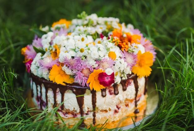 Nagi tort ozdobiony kwiatami na trawie.