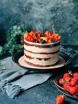Nagie ciasto z kremem, ozdobione jagodami.