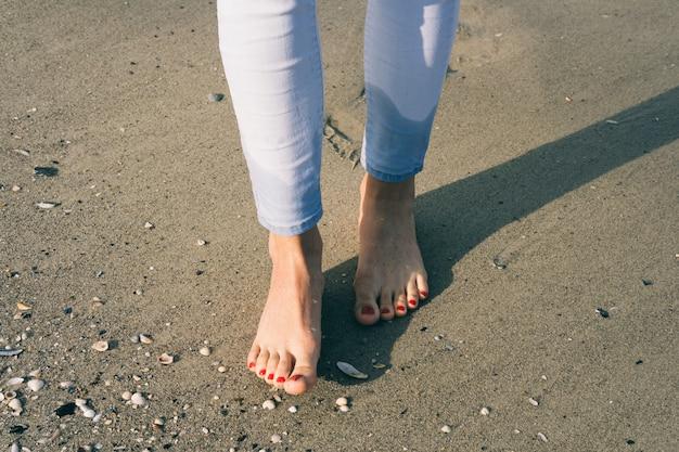 Nagie kobiece stopy chodzą na mokrym piasku na plaży