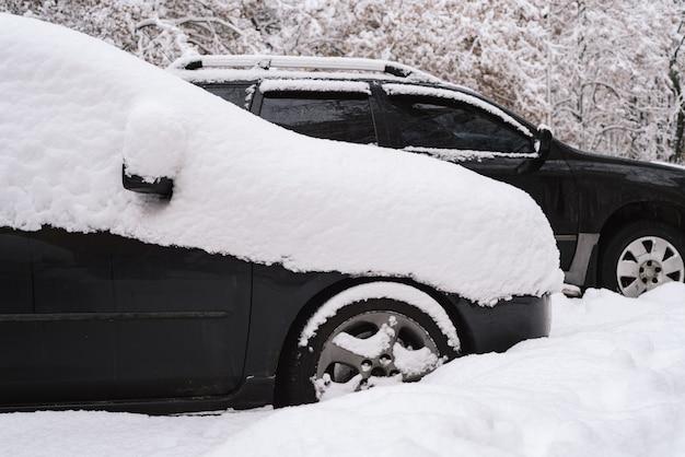 Nagłe obfite opady śniegu w mieście. samochody pokryte śniegiem. zaspy na ulicach