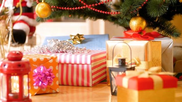 Nagranie 4k kamery powoli przesuwającej się w kierunku wielu świątecznych prezentów i prezentów leżących pod choinką na drewnianej podłodze. idealne zdjęcie na zimowe uroczystości i święta