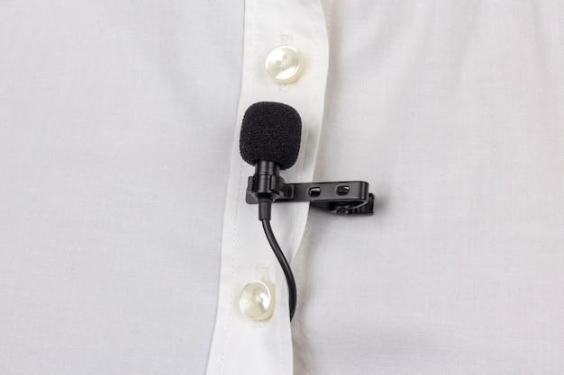 Nagranie dźwięku głosu na mikrofonie pojemnościowym. mikrofon lavalier jest zabezpieczony klipsem na białej damskiej koszuli z bliska.