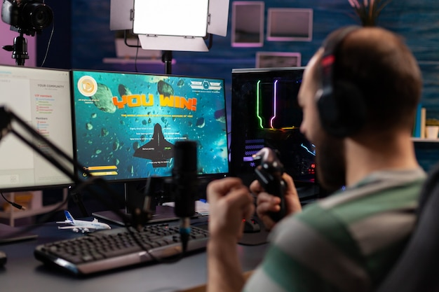 Nagranie przez ramię profesjonalnego streamera grającego w cyfrowe gry wideo na komputerze za pomocą słuchawek, mikrofonu i kontrolera. streaming man podnoszący ręce, by wygrać kosmiczną strzelankę