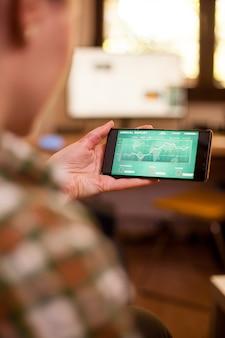 Nagranie przez ramię przedstawiające kobietę trzymającą telefon z wykresem podczas covid-19.