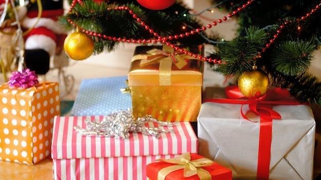 Nagranie wideo 4k przedstawiające kolorowe prezenty i prezenty leżące pod choinką w salonie i świecące świąteczne lampki. idealne zdjęcie na zimowe uroczystości i święta