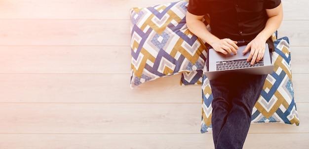 Nagranie z góry, gdy mężczyzna pracuje zdalnie za laptopem na balkonie, siedząc na poduszkach, z komputerem na nogach. zdjęcie wysokiej jakości