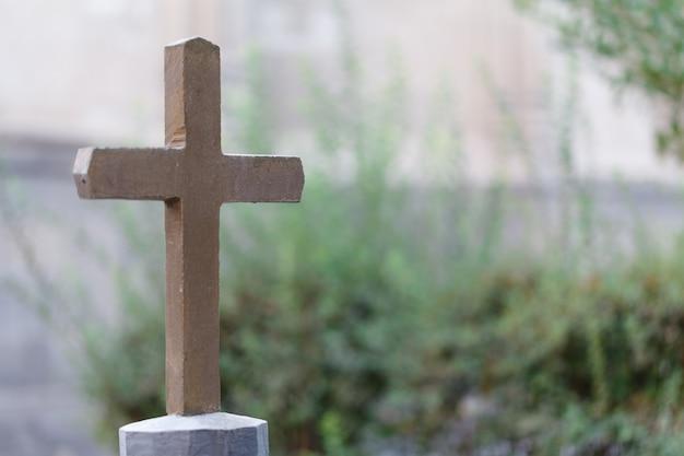 Nagrobek z pojedynczym krzyżem na cmentarzu