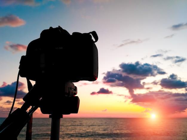 Nagrywaj filmy poklatkowe na lustrzance. słońce zachodzi nad horyzontem morza. piękny zachód słońca