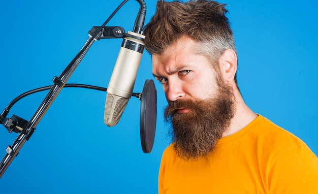 Nagrywanie człowieka w studio. brodaty mężczyzna śpiewa w mikrofonie. karaoke.