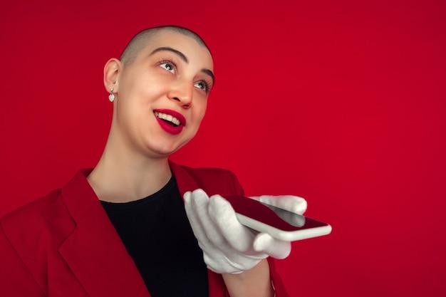 Nagrywanie głosu portret młodej kobiety kaukaski łysy samodzielnie na ścianie czerwony studio.