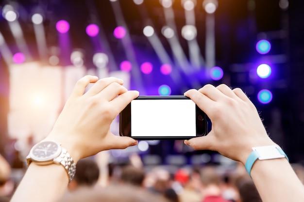 Nagrywanie koncertu przez smartfon. telefon komórkowy w uniesionych rękach. pusty ekran