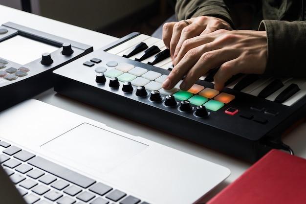 Nagrywanie ścieżki muzyki elektronicznej za pomocą przenośnej klawiatury midi na komputerze przenośnym w domowym studio