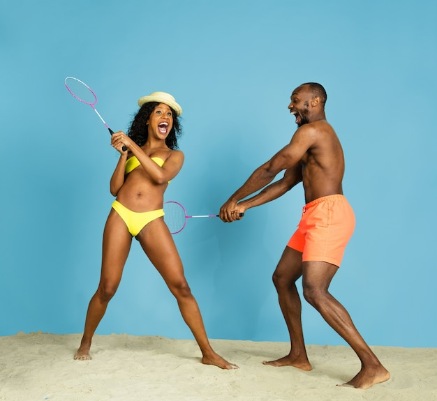 Najbardziej szalona zabawa. szczęśliwa młoda para afro-amerykańska gra w badmintona na niebieskim tle studia. pojęcie ludzkich emocji, wyrazu twarzy, wakacji lub weekendu. chłód, lato, morze, ocean.