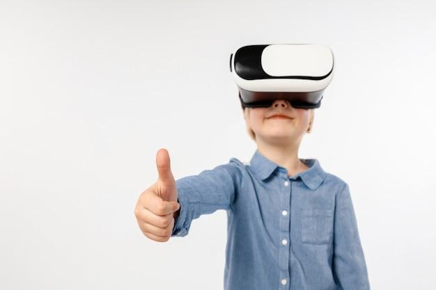 Najfajniejsze emocje. mała dziewczynka lub dziecko w dżinsach i koszuli z okularami zestaw słuchawkowy wirtualnej rzeczywistości na białym tle na tle białego studia. koncepcja najnowocześniejszych technologii, gier wideo, innowacji.
